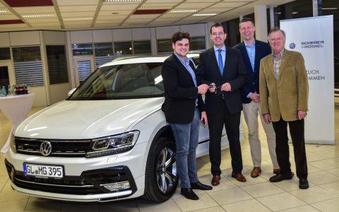 Mike Germar nimmt den Schlüssel des neuen VW Tiguan von Oliver Dörflinger in Empfang. Links davon Oliver Heiliger und Manfred Germar.