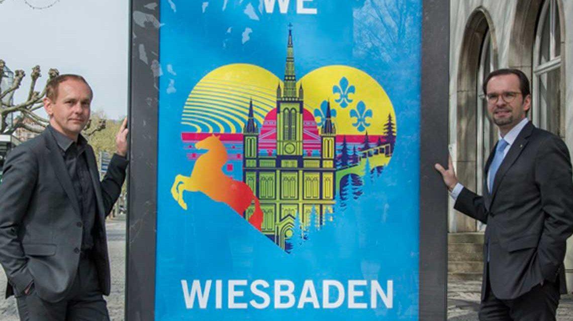 """Wall-Regionalmanager Cristian Kohut und Wiesbaden-Marketing Geschäftsführer Martin Michel vor einem der """"We love Wiesbaden"""" Plakate"""