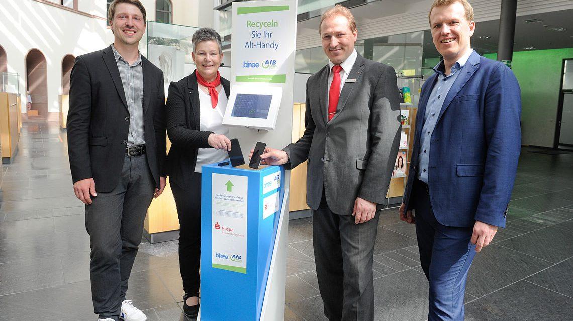 Alt-Handys werden bei der Naspa in den nächsten drei Wochen gesammelt. Martin Jaehnert (binee), Barbara Knorr, Gregor Rück (beide Naspa) und Alexander Kraemer (AfB) (v.l.n.r.) testen die Sammelbox im Wiesbadener Naspa-Stammhaus.