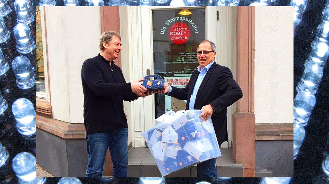 Thomas Barth (r.) von ESWE Versorgung und Peter Schumacher von der Caritas bei der Spendenübergabe vor dem Stromspar-Büro. ©2018 Flickr - ESWE / Windell Oskay - ESWE / Komposition Volker Watschounek
