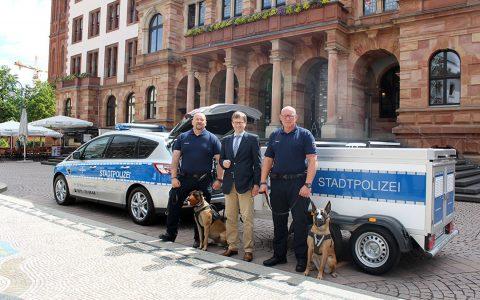 Dr. Oliver Franz mit zweiHundeführern der Stadtpolizei vor ihrem neuen Dienstfahrzeug mit Hänger. ©2018 Stadt Wiesbaden