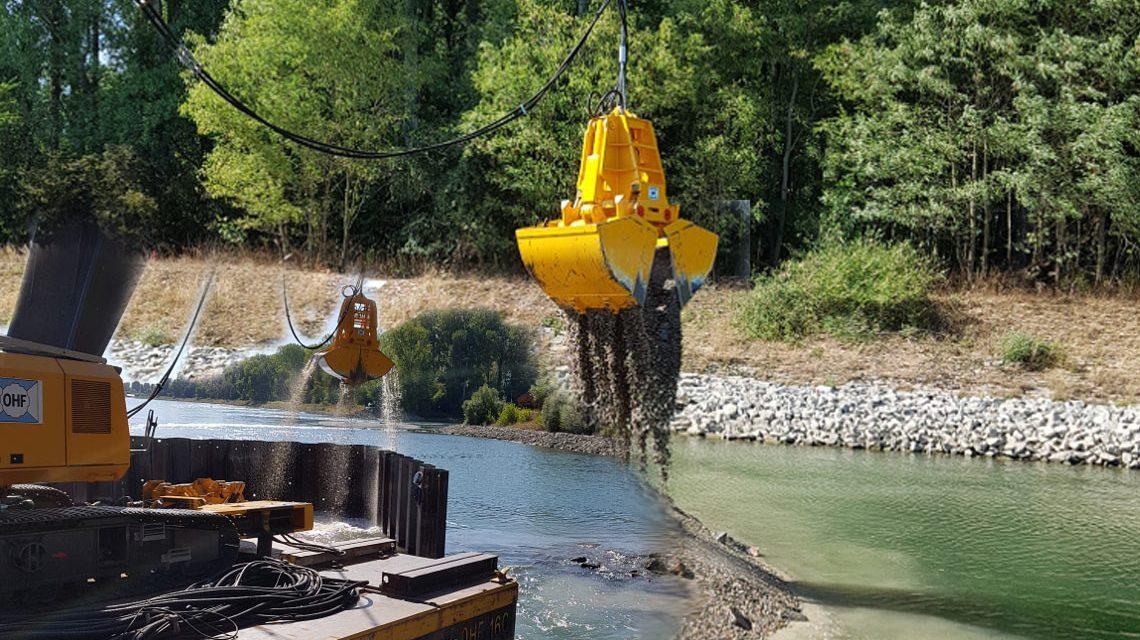 Die Schaufel leert vier Tonnen Kies aus, die vom Grund des Rheins gehoben wurden. Daneben liegen die Steine von der bereits abgetragenen Buhne.