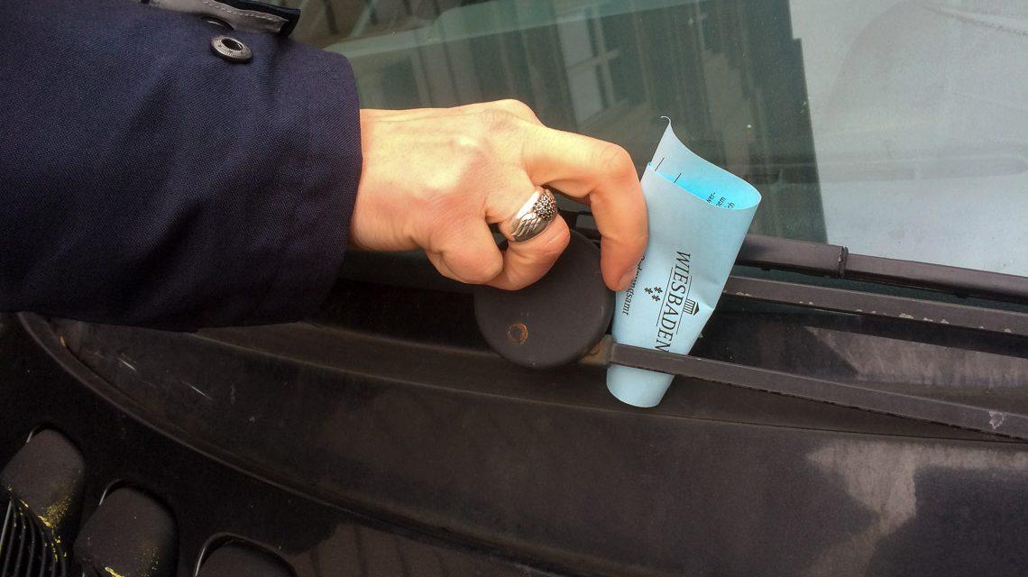 Politesse klemmt Strafzettel hinte einen Scheibenwischer.