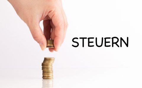 9. Steuertag der IGK Wiesbaden – Frauenhand hebt Münzen auf mit dem Text Steuern. ©2019 Marco Verch / Flickr / CC BY 2.0